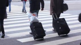 Ευρεία για τους πεζούς μετάβαση κοντά στον αερολιμένα ή το λεωφορείο/το σιδηροδρομικό σταθμό Άνθρωποι στη διάβαση πεζών απόθεμα βίντεο