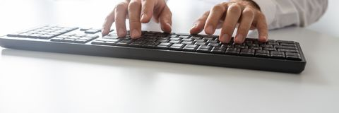 Ευρεία εικόνα άποψης του προγραμματιστή που χρησιμοποιεί το πληκτρολόγιο υπολογιστών στοκ εικόνες