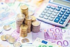 Ευρο- νομίσματα και τραπεζογραμμάτια κινηματογραφήσεων σε πρώτο πλάνο με τον υπολογιστή στοκ εικόνα
