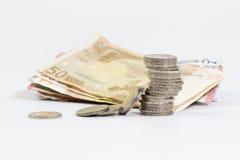 2 ευρο- νομίσματα που συσσωρεύονται και ευρο- τραπεζογραμμάτια Στοκ Εικόνες