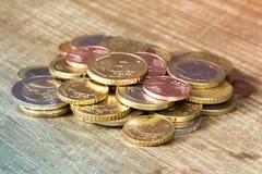 Ευρο- νομίσματα που συσσωρεύονται στον ξύλινο πίνακα Στοκ Εικόνες