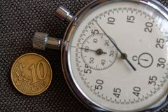 Ευρο- νόμισμα με μια μετονομασία 10 ευρο- σεντ και χρονομέτρου με διακόπτη στο καφετί σκηνικό τζιν - επιχειρησιακό υπόβαθρο Στοκ Εικόνες
