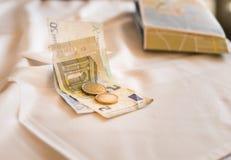 Ευρο- νόμισμα τραπεζογραμματίων μεσημεριανού γεύματος πληρωμής σε μια άσπρη επιφάνεια τραπεζομάντιλων Στοκ Φωτογραφία