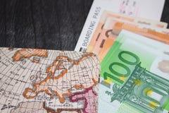 Ευρο- χρήματα, εισιτήριο αεροπλάνων και χάρτης Eurobanknotes με το πέρασμα τροφής και το χάρτη, στο μαύρο ξύλινο υπόβαθρο Στοκ Φωτογραφίες