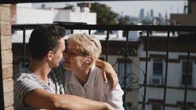 Ευρωπαία νέα γυναίκα και ισπανικός άνδρας που έχουν τον καφέ στο μικρό ηλιόλουστο μπαλκόνι με κούπες, τη συζήτηση και το χαμόγελο απόθεμα βίντεο