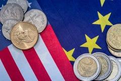 Ευρωπαϊκά και αμερικανική σημαία με τα νομίσματα στοκ εικόνες