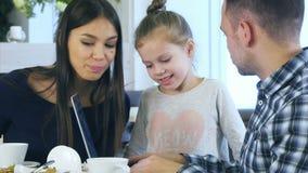 Ευρωπαϊκή οικογένεια της Νίκαιας που κοιτάζει στο lap-top και που συζητά κάτι που χαμογελά κατά τη διάρκεια του ελεύθερου χρόνου  απόθεμα βίντεο