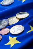 Ευρωπαϊκή σημαία και ευρο- χρήματα Ευρωπαϊκό νόμισμα νομισμάτων και τραπεζογραμματίων που τοποθετούνται ελεύθερα στην ΕΥΡ Στοκ εικόνα με δικαίωμα ελεύθερης χρήσης