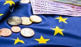 Ευρωπαϊκή σημαία και ευρο- χρήματα Ευρωπαϊκό νόμισμα νομισμάτων και τραπεζογραμματίων που τοποθετούνται ελεύθερα στην ΕΥΡ Στοκ Εικόνα