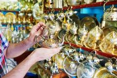 Ευρωπαϊκός τουρίστας που επιλέγει teapot στη μαροκινή αγορά Στοκ φωτογραφία με δικαίωμα ελεύθερης χρήσης