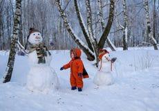 Ευρωπαϊκό αγόρι και ο χιονάνθρωπος σε ένα χιονώδες δάσος Στοκ Φωτογραφίες