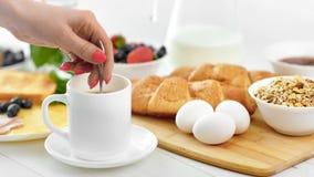 Ευρωπαϊκό θηλυκό χέρι κινηματογραφήσεων σε πρώτο πλάνο που αναμιγνύει το ποτό καφέ πρωινού στο άσπρο φλυτζάνι που χρησιμοποιεί τη απόθεμα βίντεο