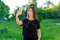 Ευρωπαϊκό κορίτσι το καλοκαίρι στο πάρκο στο καθαρό αέρα Στηρίζεται στο τηλέφωνο ακούστε μουσική Φωτογραφίες στο τηλέφωνο Στοκ φωτογραφίες με δικαίωμα ελεύθερης χρήσης
