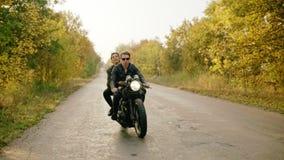 Ευρύς ακολουθώντας πυροβολισμός της οδηγώντας μοτοσικλέτας ζευγών στο δασικό δρόμο το φθινόπωρο Ελκυστικός νεαρός άνδρας στα γυαλ απόθεμα βίντεο