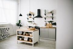 Ευρύχωρη σύγχρονη Σκανδιναβική κουζίνα σοφιτών με τα άσπρα κεραμίδια και τις μαύρες συσκευές Φωτεινό δωμάτιο r στοκ εικόνες με δικαίωμα ελεύθερης χρήσης