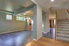 Ευρύχωρο κενό εσωτερικό με το σκοτεινό γκρίζο πάτωμα σκληρού ξύλου στοκ εικόνα