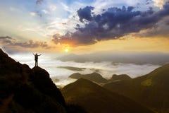 Ευρύ πανόραμα βουνών Η μικρή σκιαγραφία του τουρίστα με το σακίδιο πλάτης στη δύσκολη βουνοπλαγιά με αυξημένος παραδίδει την κοιλ στοκ φωτογραφία