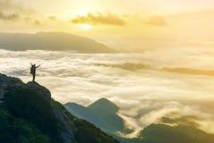 Ευρύ πανόραμα βουνών Η μικρή σκιαγραφία του τουρίστα με το σακίδιο πλάτης στη δύσκολη βουνοπλαγιά με αυξημένος παραδίδει την κοιλ στοκ εικόνες