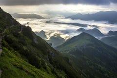 Ευρύ πανόραμα βουνών Η μικρή σκιαγραφία του τουρίστα με το σακίδιο πλάτης στη δύσκολη βουνοπλαγιά με αυξημένος παραδίδει την κοιλ στοκ φωτογραφίες