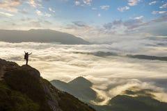 Ευρύ πανόραμα βουνών Η μικρή σκιαγραφία του τουρίστα με το σακίδιο πλάτης στη δύσκολη βουνοπλαγιά με αυξημένος παραδίδει την κοιλ στοκ φωτογραφία με δικαίωμα ελεύθερης χρήσης