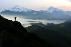 Ευρύ πανόραμα βουνών Η μικρή σκιαγραφία του τουρίστα με το σακίδιο πλάτης στη δύσκολη βουνοπλαγιά με αυξημένος παραδίδει την κοιλ στοκ εικόνες με δικαίωμα ελεύθερης χρήσης