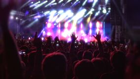 Ευτυχές άλμα ακροατηρίων και κυματίζοντας χέρια, που απολαμβάνουν την καλή μουσική στη αίθουσα συναυλιών απόθεμα βίντεο
