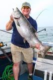 Ευτυχές άτομο με τα τεράστια ψάρια - γιγαντιαίος σολομός βασιλιάδων Στοκ εικόνα με δικαίωμα ελεύθερης χρήσης
