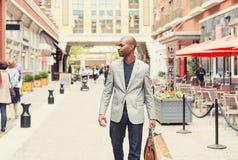 Ευτυχές άτομο με τις τσάντες αγορών που περπατά σε μια οδό Στοκ Εικόνες