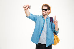 Ευτυχές άτομο με το σακίδιο πλάτης που κάνει selfie και που παρουσιάζει σημάδι ειρήνης Στοκ φωτογραφίες με δικαίωμα ελεύθερης χρήσης