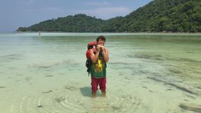 Ευτυχές άτομο οδοιπόρων με το παιχνίδι σακιδίων πλάτης τουριστών στην άρπα του στο θερμό νερό της κυανής τροπικής λιμνοθάλασσας φιλμ μικρού μήκους