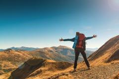 Ευτυχές άτομο οδοιπόρων με το σακίδιο πλάτης που στέκεται στην κορυφή του mountai Στοκ Φωτογραφίες
