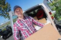 Ευτυχές άτομο παράδοσης με το κουτί από χαρτόνι με το φορτηγό Στοκ εικόνες με δικαίωμα ελεύθερης χρήσης