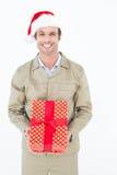 Ευτυχές άτομο παράδοσης που φορά το καπέλο Santa κρατώντας το δώρο Στοκ Φωτογραφίες