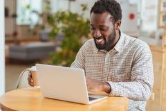 Ευτυχές άτομο που αναπτύσσει νέο app στο lap-top στον καφέ Στοκ εικόνα με δικαίωμα ελεύθερης χρήσης