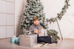 Ευτυχές άτομο που ανοίγει ένα δώρο στο σπίτι κοντά στο χριστουγεννιάτικο δέντρο στοκ εικόνες με δικαίωμα ελεύθερης χρήσης