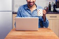 Ευτυχές άτομο που εργάζεται στο lap-top του στο σπίτι Στοκ Φωτογραφία