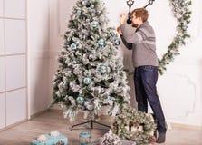 ευτυχές άτομο που διακοσμεί το χριστουγεννιάτικο δέντρο στο σπίτι στοκ εικόνες με δικαίωμα ελεύθερης χρήσης