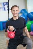 Ευτυχές άτομο που κάνει τις τεντώνοντας ασκήσεις σε μια λέσχη υγείας Στοκ Φωτογραφία
