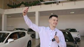 Ευτυχές άτομο που κάνει selfie τα κλειδιά εκμετάλλευσης μπροστά από το νέο αυτοκίνητό του στην αίθουσα εκθέσεως φιλμ μικρού μήκους