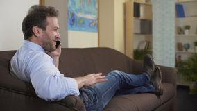Ευτυχές άτομο που κουβεντιάζει με το καλύτερο φίλο στο smartphone, που κάθεται στον καναπέ στο σπίτι απόθεμα βίντεο