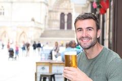 Ευτυχές άτομο που κρατά την κρύα αναζωογονώντας μπύρα του Στοκ Εικόνες