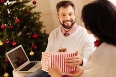 Ευτυχές άτομο που λαμβάνει το δώρο Χριστουγέννων από τη σύζυγό του Στοκ εικόνες με δικαίωμα ελεύθερης χρήσης
