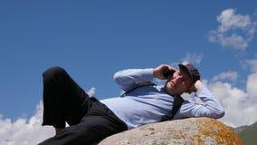 Ευτυχές άτομο που μιλά στο τηλέφωνο κυττάρων στην πέτρα φιλμ μικρού μήκους