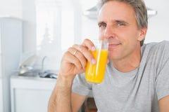 Ευτυχές άτομο που πίνει το χυμό από πορτοκάλι στην κουζίνα Στοκ Εικόνες
