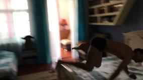 Ευτυχές άτομο που πηδά στο κρεβάτι που αφορά στο σπίτι το κρεβάτι απόθεμα βίντεο