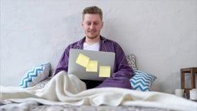 Ευτυχές άτομο που προσέχει έναν κινηματογράφο σε ένα lap-top που βρίσκεται στην κρεβατοκάμαρά του απόθεμα βίντεο