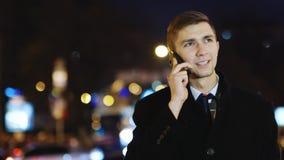 Ευτυχές άτομο που στέκεται δίπλα στην οδική κυκλοφορία και που μιλά στο κινητό τηλέφωνο, steadycam πυροβολισμός