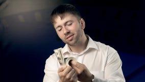 Ευτυχές άτομο που στέκεται στο μπλε κλίμα και που κοιτάζει μέσω του μεγάλου χρηματικού ποσού που έχει φιλμ μικρού μήκους