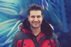 Ευτυχές άτομο που στέκεται υπαίθρια σε ένα υπόβαθρο του μπλε γυαλιού Στοκ Εικόνες