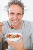 Ευτυχές άτομο που τρώει τα δημητριακά για το πρόγευμα στοκ εικόνες